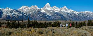 Teton mountain range panorama with three tourists looking at scene